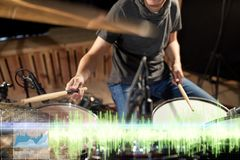 Drummer playing drum kit at sound recording studio. Music, people, musical instruments and technology concept - close up of musician with drumsticks playing drum Royalty Free Stock Images
