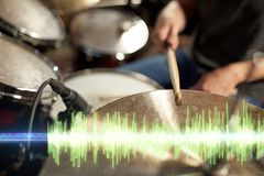 Drummer playing drum kit at sound recording studio. Music, people, musical instruments and technology concept - close up of musician with drumsticks playing drum Stock Image