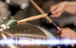 Drummer playing drum kit at sound recording studio. Music, people, musical instruments and technology concept - close up of musician with drumsticks playing drum Stock Images