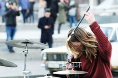 Drummer playing drums on blured city background. Street musician performing with drum. Man playing drums on the street royalty free stock images