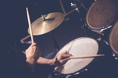 Drummer playing drums. Close up of hands of male drummer holdning drumsticks sitting and playing drums in studio royalty free stock photography