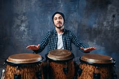 Drummer playing on wooden bongo drums, beat music. Male drummer playing on wooden bongo drums in factory shop, musician in motion. Djembe, musical percussion Stock Photo