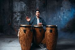 Drummer playing on wooden bongo drums, beat music. Male drummer playing on wooden bongo drums in factory shop, musician in motion. Djembe, musical percussion Stock Photography