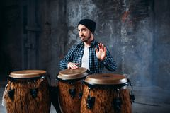 Drummer playing on wooden bongo drums, beat rhythm. Drummer playing on wooden bongo drums in factory shop, beat rhythm, musician in motion. Djembe, musical Stock Photography