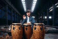 Drummer plays on african drums in factory shop. Drummer plays on african wooden drums in factory shop, beat rhythm, musician in motion. Djembe, musical Royalty Free Stock Photos