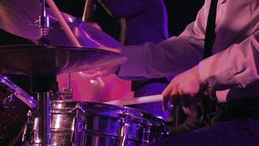 Drummer plays on drum set and cymbal slow motion. Drummer plays on drum set and cymbal with drumsticks on the stage. Jazz or rock concert performance stock video footage