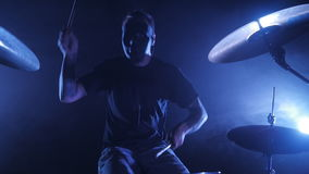 The drummer plays the drum set on the stage. Shot in a slow motion. Music video punk, heavy metal or rock group. Concert rock band performing on stage with stock video footage
