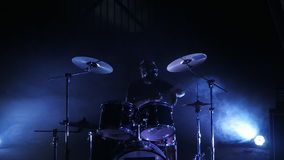 The drummer plays the drum set on the stage. Shot in a slow motion. Music video punk, heavy metal or rock group. Concert rock band performing on stage with stock video