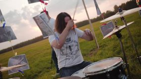 The drummer plays drums very cool. Wonderful performance of the drum part. In the open air in the field at sunset stock footage