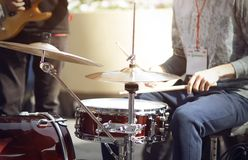 The drummer plays drumsticks on a Burgundy drum set. The drummer, one of the street musicians participating in the event, plays drumsticks on a Burgundy drum set royalty free stock images