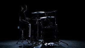 Drummer plays energetic music on the drum. Black background. Side view stock video footage