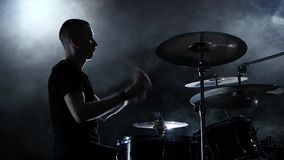 Drummer plays energetic music on the drum. Black background. Side view. Slow motion stock video footage