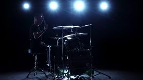 Drummer plays the melody on the drums energetically. Black background. Back light. Silhouette. Slow motion stock footage