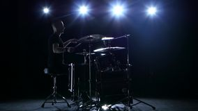 Drummer plays the melody on the drums energetically. Black background. Back light. Silhouette stock video footage