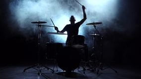 Drummer plays the melody on the drums energetically. Black background. Silhouette. Slow motion stock footage