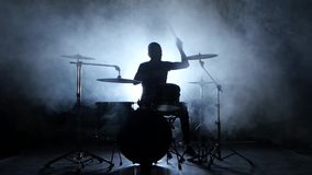 Drummer plays the melody on the drums energetically. Black background. Silhouette stock video footage