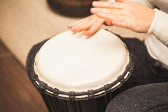 Drummer plays on small African drum. Closeup photo with selective focus Stock Photography