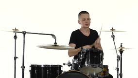 Drummer plays vigorous music on a drum set. White background. Slow motion stock video footage