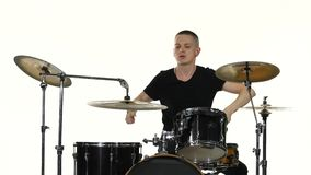 Drummer plays vigorous music on a drum set. White background. Drummer plays well energetic, cheerful music on a professional drum set using drum sticks sitting stock footage