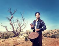 Drummer plays on wooden bongo drums in desert. Young male drummer plays on wooden bongo drums in desert, musician in motion. Djembe, musical percussion Royalty Free Stock Photos