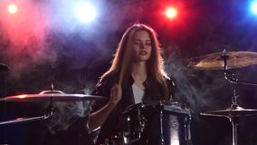 Drummer professionally plays a musical instrument. Black smoke background. Red blue light from behind. Drummer professionally plays a musical instrument, she stock footage