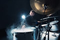 Drummer rehearsing on drums before rock concert. Man recording music on drum set in studio. With show effect in the form of flour Stock Images