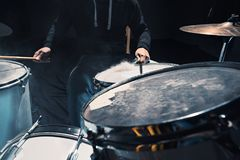 Drummer rehearsing on drums before rock concert. Man recording music on drum set in studio. With show effect in the form of flour Stock Photos