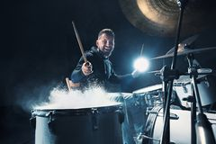 Drummer rehearsing on drums before rock concert. Man recording music on drum set in studio. With show effect in the form of flour royalty free stock image