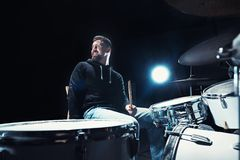 Drummer rehearsing on drums before rock concert. Man recording music on drum set in studio. With show effect in the form of flour Royalty Free Stock Images