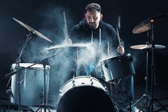 Drummer rehearsing on drums before rock concert. Man recording music on drum set in studio. With show effect in the form of flour royalty free stock photography