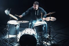 Drummer rehearsing on drums before rock concert. Man recording music on drum set in studio. With show effect in the form of flour Stock Photo