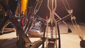 Drummer`s foot in sneakers moving drum bass pedal Royalty Free Stock Images