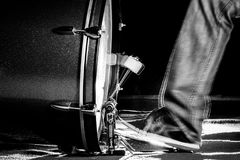 The drummer`s foot wears sneaker is playing bass drum pedal. In low light background, black and white Royalty Free Stock Image