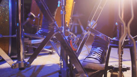 Drummer`s foot wears sneakers moving drum bass pedal Royalty Free Stock Photos
