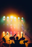 Drummer silhouette on a stage. Drummer silhouette at colorful backlights on a stage with the hands raised up with drumsticks Stock Photos