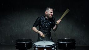 The drummer on the drum wooden sticks and water drops flying in all directions. stock footage