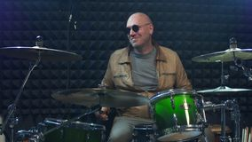 Drummer in sunglasses playing drums at performance. Drummer solo rock concert stock footage