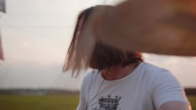The drummer is very expressive pounding the drums. Very powerful performance. Playing at sunset in the field. Very beautiful momen. T. Rock music stock video footage