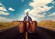 Drummer with wooden drums plays on desert road. Young male drummer with wooden bongo drums plays on desert road, musician in motion. Djembe, musical percussion Stock Photo