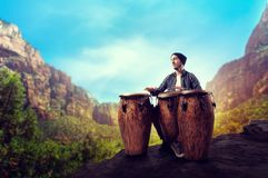 Drummer with wooden drums plays in desert valley. Young male drummer with wooden bongo drums plays in desert valley, musician in motion. Djembe, musical Stock Image