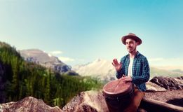 Drummer with wooden drums plays on top of mountain. Young male drummer with wooden bongo drums plays on top of mountain, musician in motion. Djembe, musical Royalty Free Stock Image