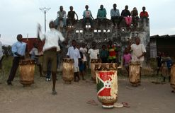 Drummers in Burundi. People of various ages playing the drums, behind them children are sat on top of a wall looking down at the drummers Stock Images