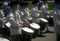 Drummers in white colonial uniforms march Royalty Free Stock Photos