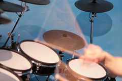 Drumming Action. Motion of drummer's hands and drumsticks as he plays fast rhythms in the studio Royalty Free Stock Photography