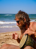 Drumming the silence. Man drums on tam-tam on the beach Royalty Free Stock Photos