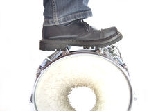 Drums conceptual image. Leg standing on overturned snare Royalty Free Stock Image