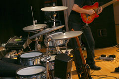 Drums and guitarist. Close-up view of a drum kit and guitarist on stage Stock Image