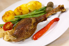 Drumstick of baked Goose with green beans,potatoes Stock Photos