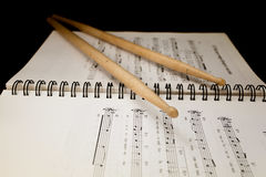 Drumsticks on musical notes Royalty Free Stock Images
