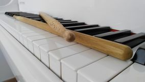 Drumsticks on a piano Stock Photo
